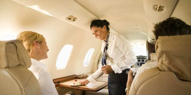 Flight attendant offering dessert to businesswoman on airplane